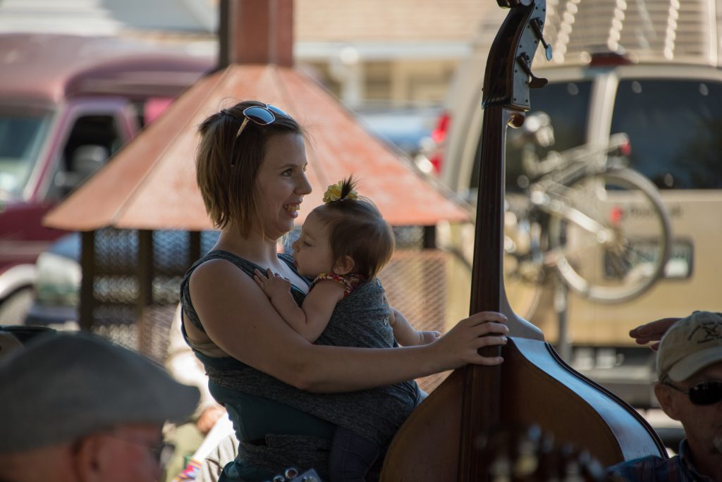 cellist mom holds her baby while playing cello